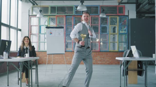 A young businessman enters the office with a reward in his hands. Colleagues join, dance with him and blow up flappers with confetti. Co-working in loft style. Office life. Winners video
