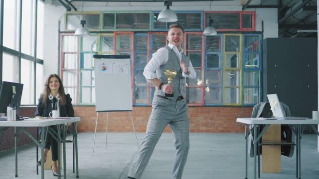 Ein junger Geschäftsmann betritt das Büro mit einer Belohnung in der Hand. Kollegen kommen dazu, tanzen mit ihm und sprengen Flapper mit Konfetti. Co-Working im Loft-Stil. Büroleben. Gewinner – Video