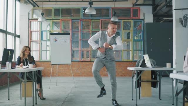 Junger Geschäftsmann lustig tanzen im Büro. Kollegen sitzen an den Tischen und tanzen im Sitzen. Kreative Büroräume im Loft-Stil. Büroleben. Die Arbeiter feiern. Co-Working – Video