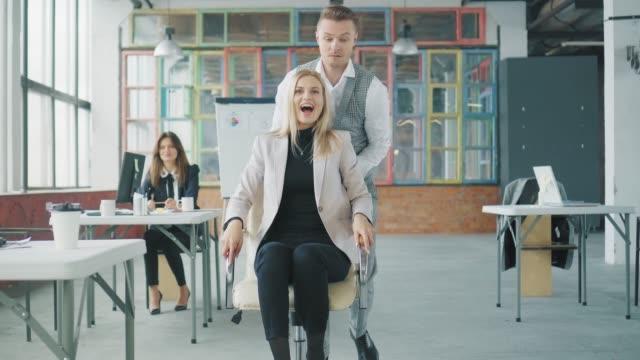 若いビジネスマンがオフィスを回り、従業員が椅子で彼を迎えに行き、ビジネスマンが同僚を迎えに行き、楽しそうに転がります。コワーキング。オフィスエンターテイメント。クリエイテ� ビデオ