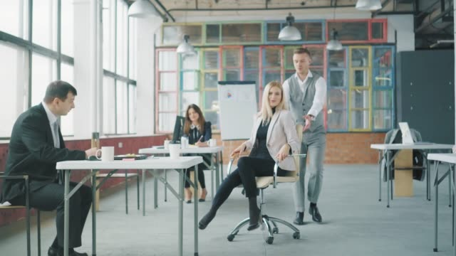 A young businessman goes around the office, an employee rolls out to meet him on a chair, he picks it up and rolls it cheerfully around the office. Co-working. Office life. Creative interior video