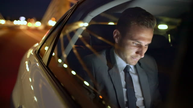 ms young businessman greeting someone while driving in the back seat of a car - attrezzatura informatica video stock e b–roll
