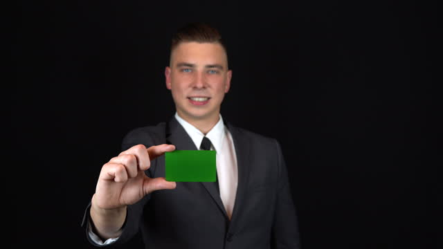 A young businessman in a suit holds a bank card in hand. Isolated black background. Chromakey green card.