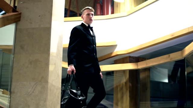 Jeune homme d'affaires dans un costume avec un nœud papillon va vers le bas de l'escalier tenant sac grand en cuir noir. Slowmotion - Vidéo