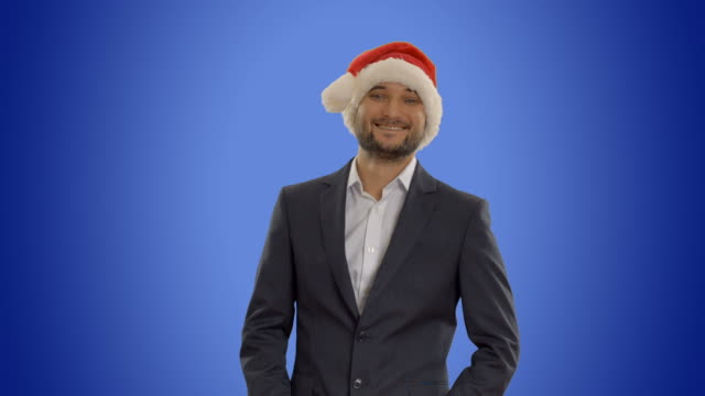 young businessman in hat of Santa Claus on blue background video