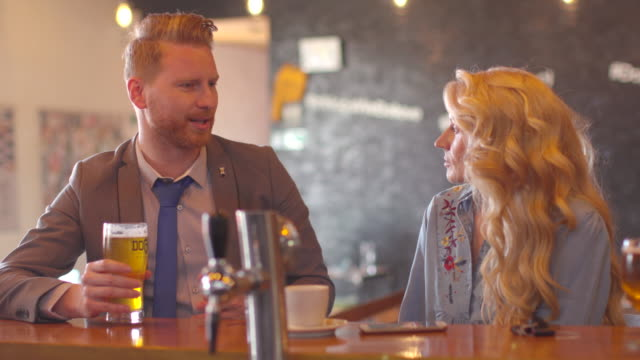 Young businessman in relaxed conversation with woman at the bar