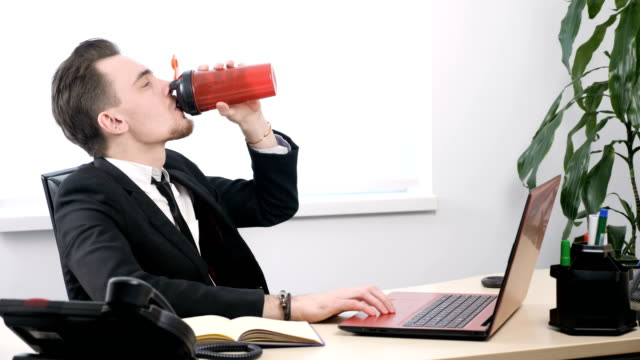 Young businessman in suit drinks from sports shaker sitting in office 60 fps video