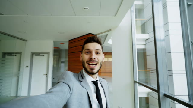 pov of young businessman in suit having online video chat using smartphone camera and talking to his colleagues in modern office - video call video stock e b–roll
