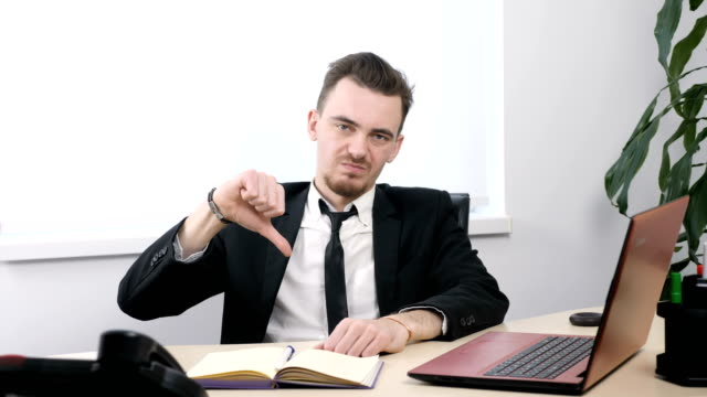 Young businessman in suit sitting in office and showing thumbs up sign 60 fps video