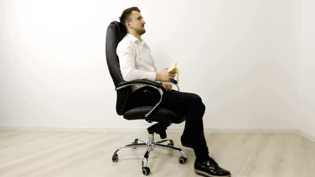 A young businessman is sitting in an office chair and eating a banana. video