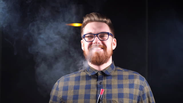 Young businessman is tasting a new hookah
