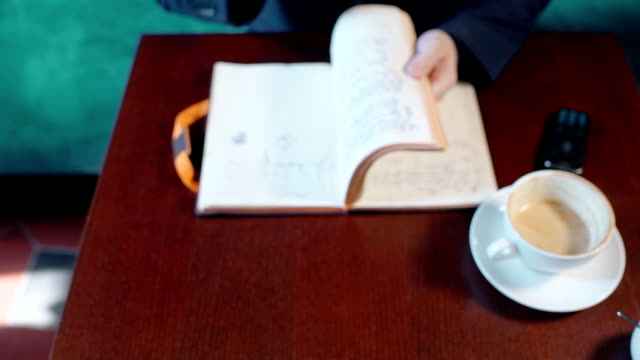 Young businessman is working with notebook, sitting at table in cafe interior video