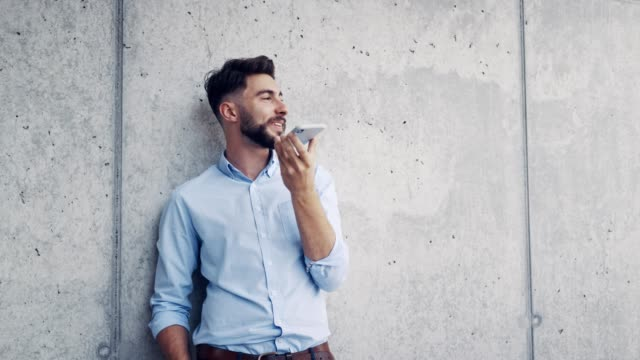 Young businessman leaning against wall and talking on phone with speaker mode Young businessman leaning against wall and talking on phone with speaker mode leaning stock videos & royalty-free footage