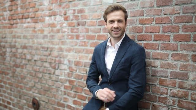 vídeos de stock, filmes e b-roll de jovem empresário apoiado em uma parede de tijolos com as mãos cruzadas e olhando de lado, sorrindo, de pé com as mãos no bolso e olhando para baixo - braço humano