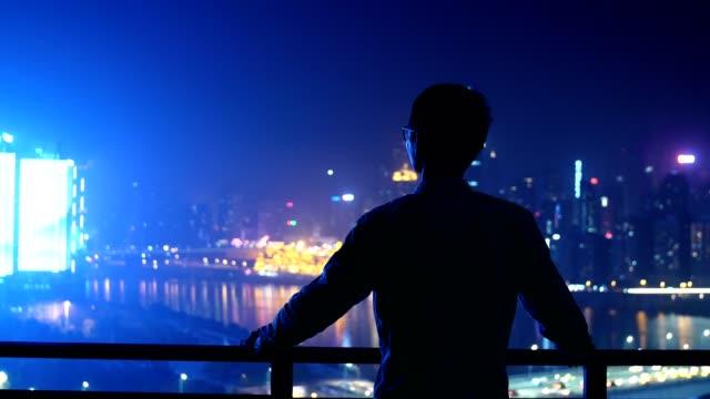 vídeos de stock, filmes e b-roll de jovem empresário, olhando a noite da cidade - distante