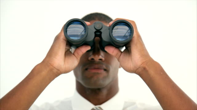 Young businessman looking through binoculars video