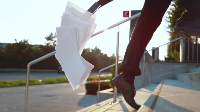 階段を全力疾走しながら書類を失うスローモーション効果: 青年実業家 - 不吉点の映像素材/bロール
