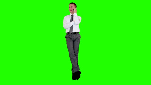 Young businessman on mobile and sitting, Green Screen