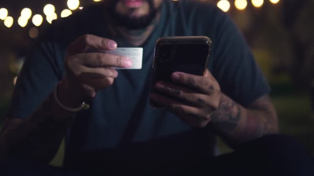young businessman paying bills and using online banking on mobile phone at cafe. bangkok, thailand. - fare una prenotazione video stock e b–roll