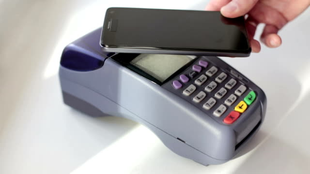 Young businessman pays using NFC wireless system in a restaurant - vídeo