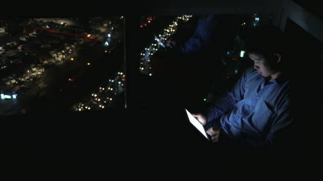 Young businessman playing game on tablet computer at night video