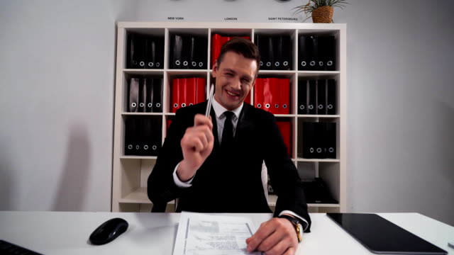 Young businessman pointing and laughing with Your funny joke video