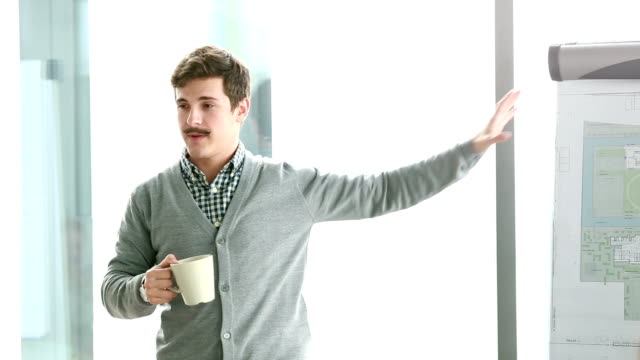Young businessman pointing at flipchart during presentation video