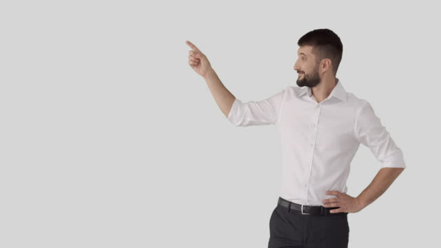 Young businessman pointing finger at white background Smiling businessman pointing finger and showing blank copy space over white background arms akimbo stock videos & royalty-free footage