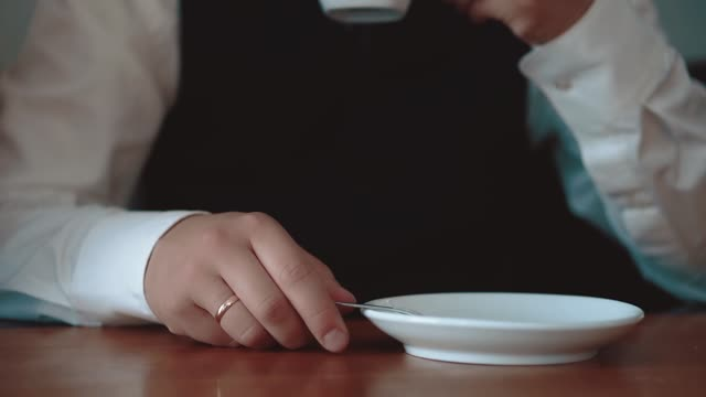 Young businessman pours sugar into a mug with coffee, close-up