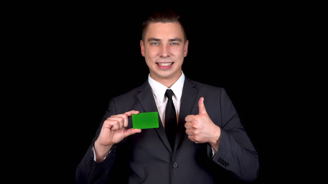 Young businessman presents a bank green card and shows like with his hand. Chromakey green card. Man in a black suit on a black background