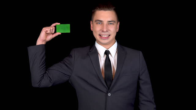 A young businessman presents a green bank card. Chromakey green card. Man in a black suit on a black background