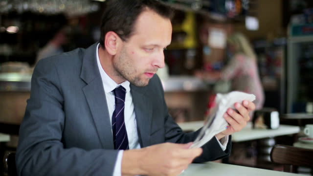 Young businessman reading bad news in newspaper, steadicam shot video