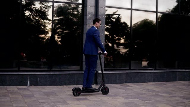 young businessman riding an electric scooter for a business meeting in the office, office buildings, business man, electric transport, ecological transport. side view - monopattino elettrico video stock e b–roll