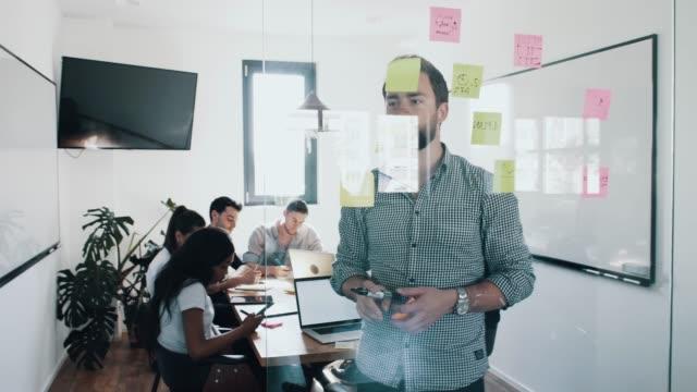 ung affärsman dela strategi plan affärsidé med kollegorna och skriva anteckningar ner på papper och sätta post-it papper på vita tavlan under mötet på moderna kontor - whiteboardtavla bildbanksvideor och videomaterial från bakom kulisserna