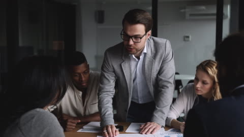 Young businessman sharing company development ideas with diverse partners. Confident young businessman in eyeglasses leaning over table sharing company development ideas with diverse partners, writing notes on research reports documents at brainstorming meeting in office. determination stock videos & royalty-free footage