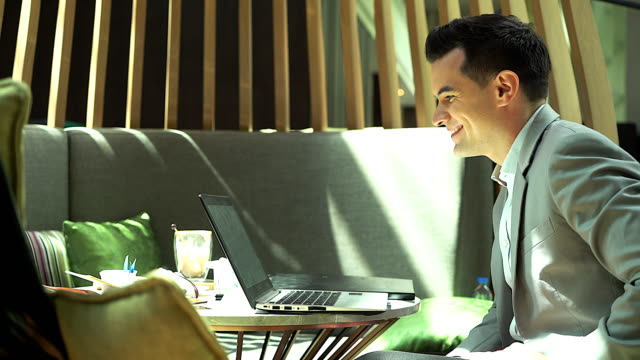Young businessman sitting in cafe while using laptop computer to conference call.