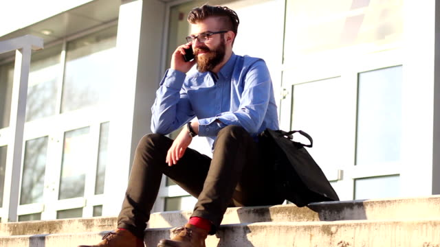Young businessman sitting on stairs and talking on the phone video