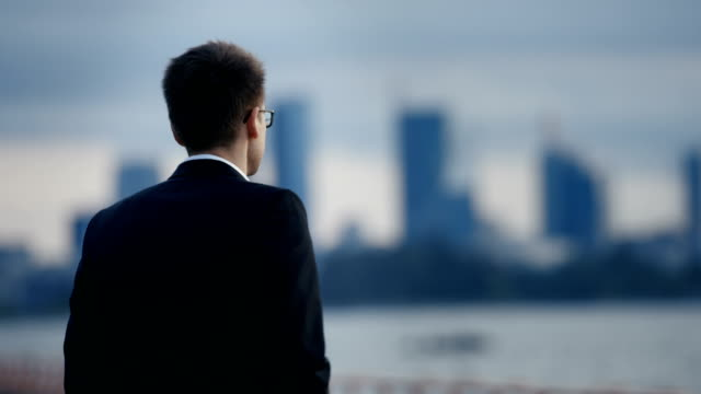 Young Businessman Stands at the Seashore Contemplating His Career and Life Choices then Starts Walking Towards the Big City. In the Background Big City View with Skyscrapers Visible. video