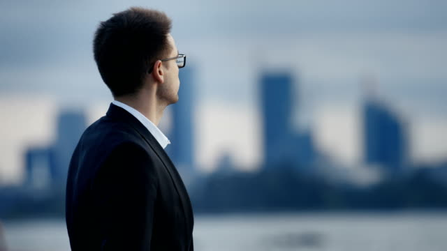 Young Businessman Stands at the Seashore Contemplating His Career and Life Choices. In the Background Big City View with Skyscrapers Visible. Young Businessman Stands at the Seashore Contemplating His Career and Life Choices. In the Background Big City View with Skyscrapers Visible. Shot on RED EPIC-W 8K Helium Cinema Camera. mid adult men stock videos & royalty-free footage