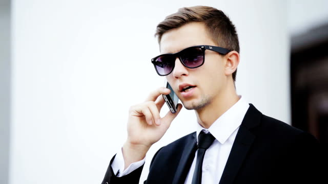 Young businessman talking on cell video