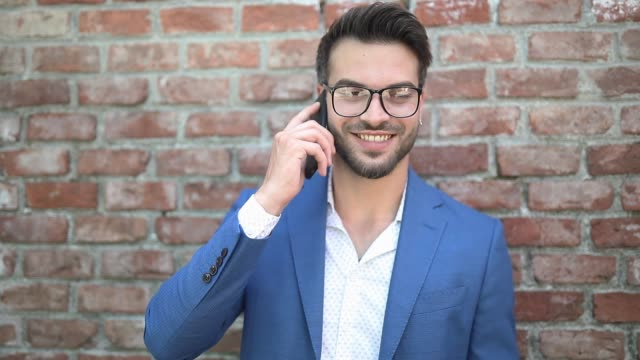young businessman talking on the phone, smiling, looking aside, texting and leaning on a brick wall