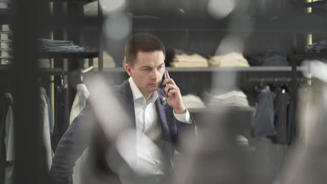 Young businessman talking over the phone in the luxury brand exclusive male clothing shop. video
