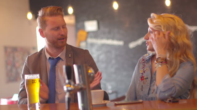 Young businessman talking relaxedly with woman at the bar