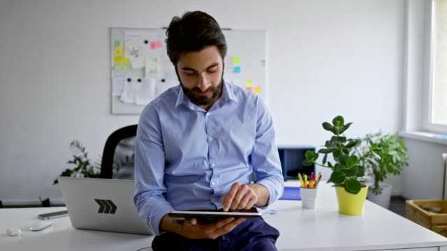young businessman talking through wireless headphones while using tablet in office - cuffie wireless video stock e b–roll