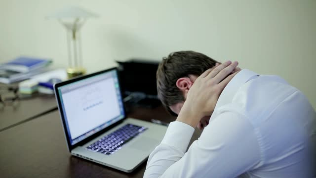 Young businessman tired of working on laptop video