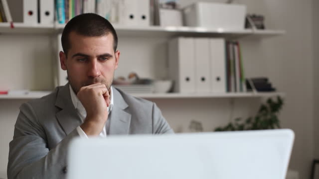 Young businessman typing at laptop in office