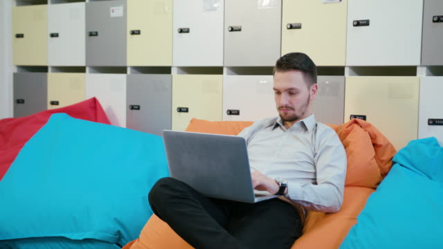 A Young Businessman Using a Laptop Indoors