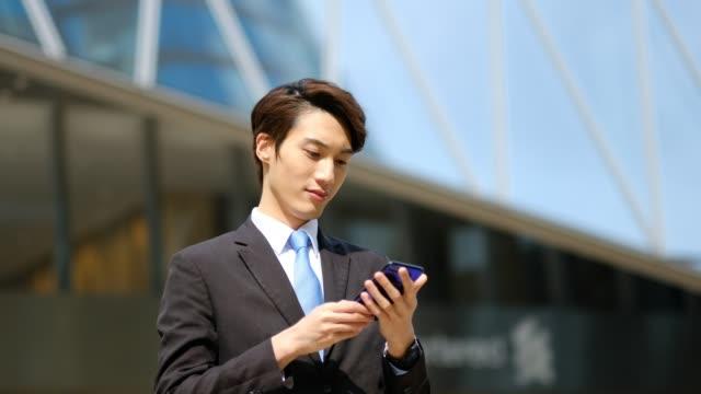 stockvideo's en b-roll-footage met jonge zakenman met zijn telefoon buitenshuis - oost azië