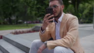 istock Young businessman using mobile phone and relaxing at public park 1244073486