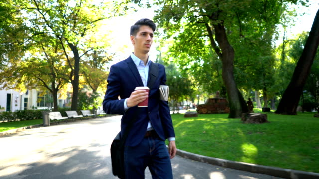 Young businessman walking and holding coffee and newspaper video